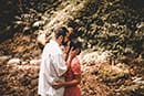 Man kissing womans forehead during engagement photoshoot in forest