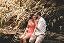 Man caressing face of bride to be in red floral dress Ka'au Crater Trail